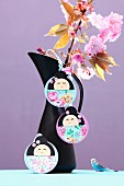 Hand-crafted, Japanese Kokeshi pendants on jug holding branches of cherry blossom