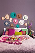 A double bed with various different coloured cushions against a purple wall hung with hats