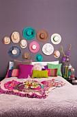 Doppelbett mit verschiedenfarbigen Kissen vor lila Wand und aufgehängter Hutsammlung