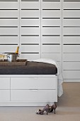 Ladies' shoes and half-height chest of drawers with upholstered top in front of white fitted cupboards with slotted doors