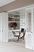 Partially open, white folding doors with view of chair at rustic wooden table and modern fitted cupboards
