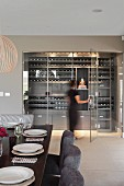 Set dining table and dining chairs with grey covers; woman walking into illuminated wine store behind glass doors