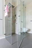A floor-level, tiled shower cubicle with a rain shower and a hand-held shower head with a glass partition wall in a designer bathroom