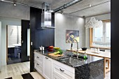 Kitchen counter with granite worksurface next to open, black sliding door