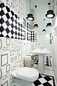 Toilet decorated in black and white with top-hat pendant lamps and and illusion of space produced by mirrored wall behind pedestal sink