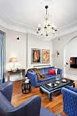 Blue sofa set and reading chair with blue leather cover around coffee table below chandelier in traditional living room