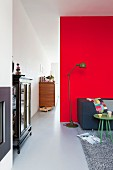 Retro standard lamp next to couch against partition wall covered in red felt; antique, glass-fronted cabinet to one side