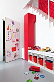 Play area; open-fronted sideboard with red storage boxes and door covered in child's drawings