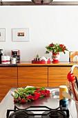 Ausschnitt einer Kochinsel, rote Tulpen auf Edelstahl Arbeitsplatte, gegenüber Sideboard aus hellem Holz