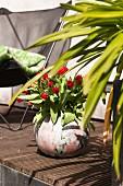 Red tulips in spherical vase on wooden terrace floor