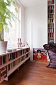 Bookshelves below window and narrow, cylindrical, white standard lamp in modern interior