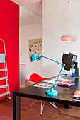 Pale blue, retro table lamp on black desk opposite red wall in modern interior