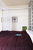 Modern four-poster bed with metal frame and dark bedspread against accent wall with patterned wallpaper