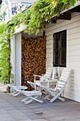 Ruheplatz mit weissen Deckchairs und Beistelltisch vor eingeschossigem Anbau mit Brennholznische und rankender Glyzine