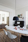 Black pendant lamp above white, oval table an shell chairs; piano and sofa in adjoining living area in background