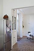 Notizen mit Magnet-Pins an Edelstahlkühlschrank, Blick in den Essraum mit Stuckdecke, einfachem Dielenboden und Einbau-Vitrinenschränken