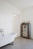 Vintage cupboard next to bathroom door; free-standing clawfoot bathtub with retro tap fittings
