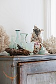 Vases, glass containers and flotsam on old cabinet in bathroom