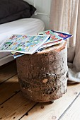 Comics on tree stump table on castors used as bedside table, stripped wooden floor, metal bed and floor-length linen curtains