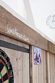 'Good night' written in chalk in Dutch (Welterusten) on board wall in teenager's bedroom with dartboard in foreground