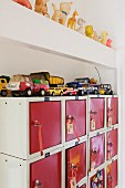 Old toy cars on top of salvaged locker cabinet with red doors; row of small squeaky toys on beam