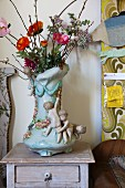 Eclectic furniture and accessories; china vase decorated with garlands and children next to wall panel with 70s floral pattern