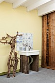Sink area in conservatory extension furnished with old Delft tiles, branch sculpture, retro sink and washstand made from wooden boards