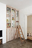 Old wooden ladder in front of fitted cupboard with doors made from wooden boards and glass