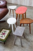 Wooden stools, 50s side table, footstool with floral, tapestry cover and leather swivel armchair on concrete floor
