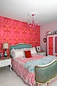 Rococo-style double bed and bedside tables in bedroom painted pale pink with deep pink, large-patterned wallpaper on accent wall