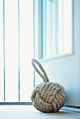 Ball of cord with loop used as door stop for open door