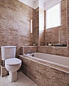 Masculine atmosphere in simple, beige, marble bathroom with tiled walls, bathtub below window and traditional, white toilet with cistern