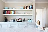 Blick über Marmortischplatte auf eingebautes Sideboard in Wandnische mit zwei weißen Wandboards für Bücher und Wohnaccessoires mit Vintage-Flair