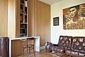 Braune Ledersessel unter Bild, seitlich Einbauschrank aus Holz und integrierter Schreibtisch, davor Thonetstuhl