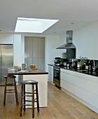 Rustic bar stools at breakfast bar below skylight in modern kitchen