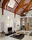 Contemporary interior with lounge furnishings in former church nave with Gothic-style windows and exposed roof structure