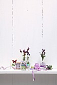 Sprigs of lavender in glass bottles decorated with ribbons and washi tape on surface against whitewashed wooden wall