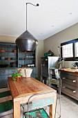 Holztisch und Edelstahlschränke in einer Küche mit Vintage Interieur