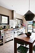 Vintage pendant lamp above dining table and metal chairs in front of kitchen counter with stainless steel cabinets