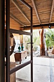 View through open lattice door of wooden trunk on roofed terrace and garden