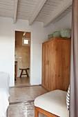 Körbe auf Holzschrank und Polsterstuhl in mediterranem Schlafzimmer mit Holzdecke