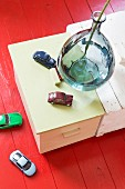 Glass vase and toy cars on wooden trunk and on red-painted wooden floor