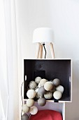Garland of lanterns in various shades of grey in shelf compartment; table lamp with white lampshade on top