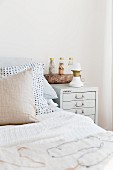 Scatter cushions on bed next to table lamp on bedside cabinet