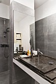 Grey-tiled designer bathroom with minimalist washstand on mirrored partition screening shower