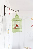 Metal bird ornaments in green vintage birdcage hanging from metal wall bracket