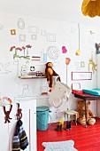 Stofftiere auf Wandbord und unter dem Tisch auf rot lackiertem Dielenboden im Kinderzimmer