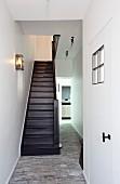 Schmales Treppenhaus mit Steinboden; seitlich die renovierte Eingangstür