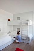 Zwei übereck gestellte Betten und ein Hochbett im weissen Kinderzimmer; Junge vor Stauraumschublade