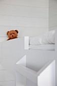 Teddybär auf einem Hochbett mit Bettleiter